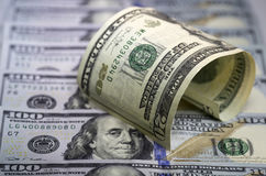 Arched twenty us dollar bill standing on lined hundred us dollar bills background. Selective focus Stock Photography