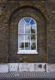 Arched warehouse window. Yellow brick arched warehouse window with white frame Stock Photos