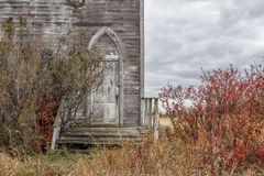 An arched weathered grey church door. An arched church door and steps on a weathered grey church with red shrubs beside it Stock Photography