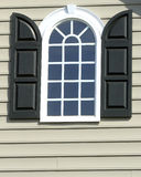 Arched Window with Black Shutters Stock Photos