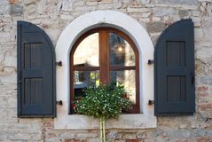 Arched window and daisies on the window sill in the village of Strassoldo Friuli (Italy) Royalty Free Stock Photography