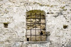 Arched window with metal bars in old stonework. The ancient half-ruined synagogue royalty free stock image