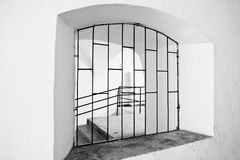 Arched window with metal grating. Black and white Stock Images