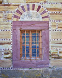 Arched window on  red and ocher colored stone wall Stock Photo
