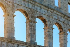 Arched windows of an ancient Roman amphitheater against the blue sky.  Stock Photo