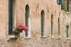 Arched windows and flowers in Italy. Royalty Free Stock Photo