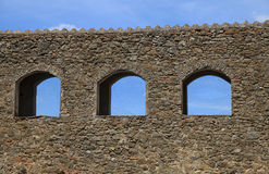 Arched windows in ruin stone wall against a blue sky, Italy. Detail of exterior arched windows in ruin stone wall against a blue sky, Italy Royalty Free Stock Photos