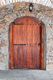 Arched wooden door in a stone wall Stock Photos