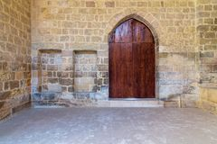 Arched wooden door and two embedded niches in stone bricks wall, Old Cairo, Egypt. Arched wooden door and two embedded niches in stone bricks wall, at the public stock photo