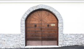 Arched wooden doors, stone frame. Gray, brown Stock Photo