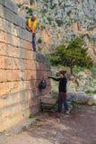 Archeologen die aan de plaats in oud Delphi werken - mens vuil verlagen en meisje die door het ziften en het carting weg Delp royalty-vrije stock foto's