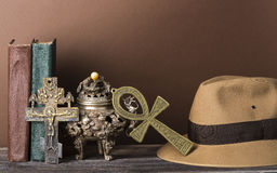 Archeological and adventure concept for lost artifacts with hat, vintage books, iron vase, key of life, vintage cross Stock Image