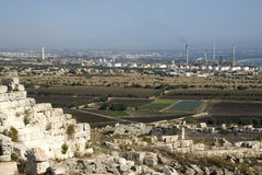 Archeological site and factories at horizon. Agriculture, history and factories in the island of Sicily Stock Photo