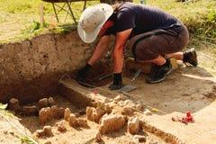 Archeologische hulpmiddelen, Archeoloog aan plaats werken, hand en hulpmiddel die stock afbeelding