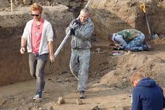 Archeologische uitgravingen De archeologen in een graafproces, die het graf met menselijke beenderen onderzoeken, die met maatreg royalty-vrije stock afbeelding