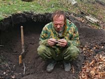 Archeologist 2. The men in ground  pit explores his find. The state inspector of nature reserve Lazovsky is archeologist amateur. He explores new places for Royalty Free Stock Photo