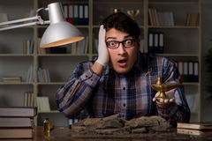 The archeologist working late night in office Stock Photos