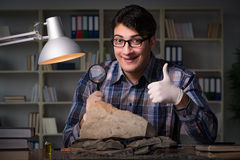 The archeologist working late night in office Stock Photo
