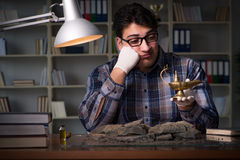 The archeologist working late night in office Royalty Free Stock Photography