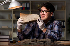 The archeologist working late night in office Royalty Free Stock Photo