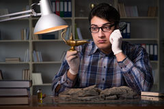 The archeologist working late night in office Stock Photography
