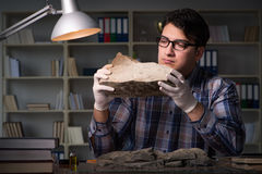 The archeologist working late night in office. Archeologist working late night in office Royalty Free Stock Photography