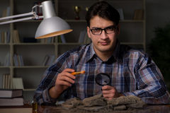 The archeologist working late night in office Stock Images