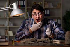 The archeologist working late night in office Stock Image