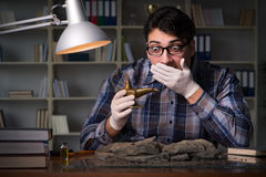 The archeologist working late night in office. Archeologist working late night in office Royalty Free Stock Photo
