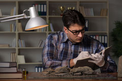 The archeologist working late night in office. Archeologist working late night in office Stock Images