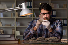 The archeologist working late night in office. Archeologist working late night in office Stock Photos