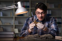 The archeologist working late night in office. Archeologist working late night in office Stock Image