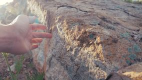 Archeology concept. Man touches hands stone granite rock sunlight. Lifestyle nature wild ancient the rock stone. Archeology concept. Man touches hands stone stock video