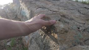 Archeology concept. man touches hands stone granite rock sunlight. Nature wild ancient rock stone lifestyle. Archeology concept. man touches hands stone granite stock video footage