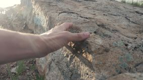 Archeology concept. man touches hands stone granite rock sunlight. Nature wild ancient the rock lifestyle stone. Archeology concept. man touches hands stone stock video