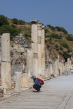 Archeology learning in Ephesus Turkey. A tourist is watching carefully to a column in the antique greek, later roman, city of Ephesus; in the actual Turkey Royalty Free Stock Photography