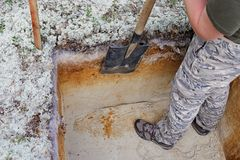 Archeology: rough cleaning of the excavation wall. Archeology : alignment of the excavation wall by hand using a shovel Stock Image
