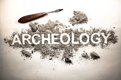 Archeology word written in letters on a pile of ash, dirt, soil,. Archeology word written in letters on a pile of grey ash, dirt, soil, ground as excavation of Stock Image