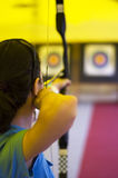 Archer. Girl aiming her arrow to the bull's eye Royalty Free Stock Images