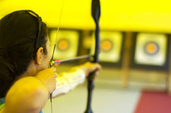 Archer. Girl aiming her arrow to the bull's eye stock photography