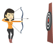 Archer aiming with bow and arrow at the target. Stock Photo