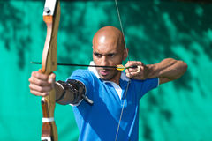 Archer aiming at target with bow and arrow Royalty Free Stock Images