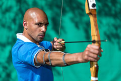 Archer aiming at target with bow and arrow Royalty Free Stock Image