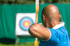 Archer aiming at target with bow and arrow Stock Images