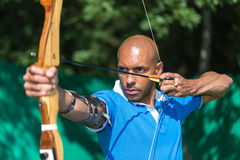 Archer aiming at target with bow and arrow. Bowman or archer aiming at target with bow and arrow Royalty Free Stock Images