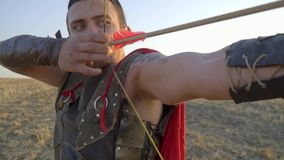 The archer in the armor holds the arrow on the string on his knee in the middle of the field, slow motion