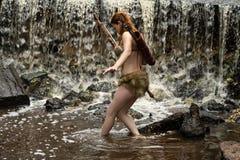 Archer beweegt de stroom van water met een in hand boog royalty-vrije stock afbeeldingen