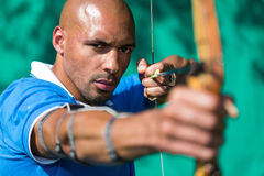 Archer che punta su obiettivo con l'arco e la freccia Fotografie Stock