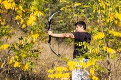 Archer die zijn bomen van de samenstellingsboog trekken stock fotografie