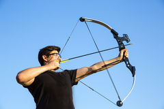 Archer drawing his compound bow blue sky Royalty Free Stock Photography